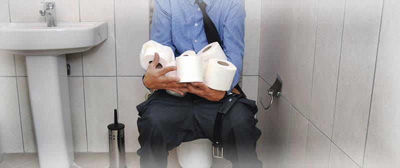 mand paa toilet med ondt i maven og virkelig meget toiletpapir
